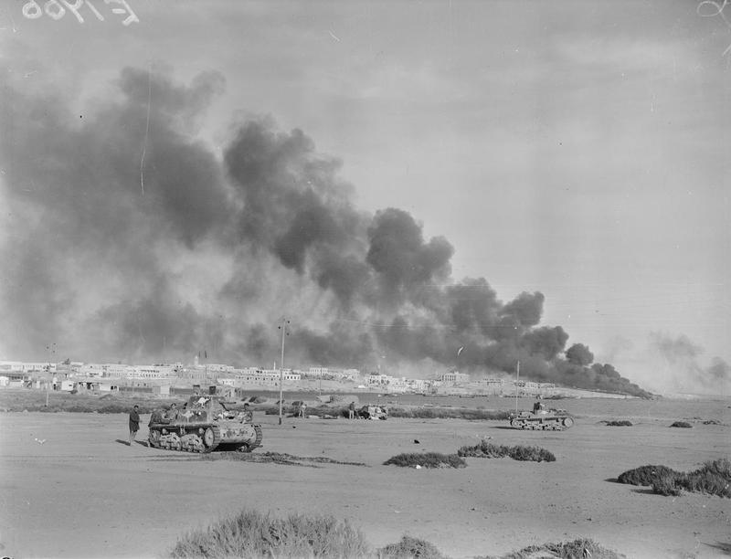 Port installations burn over the harbour town of Tobruk, 24 January 1941 (IWM E1766)